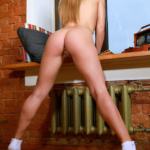 Lovely Latvian blonde Sarika A bends over the desk nude looking very spankable